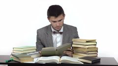 young reading student is sitting at table surrounded by books. - stock footage