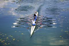 Four women rowing on the tranquil lake Stock Photos