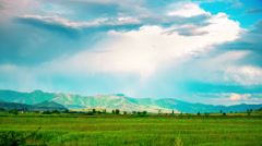 Countryside scenery beautiful landscape clouds sky green wheat fields mountains Stock Footage