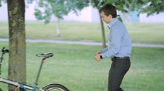 Businessman unlock bicycle from a tree Stock Footage