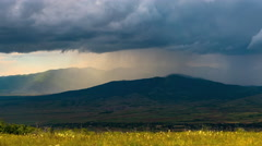 Beautiful dramatic landscape storm heavy rain sun beams mountains clouds Stock Footage
