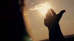 Girl looks at the sun through her hand Stock Footage