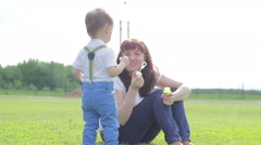 Baby boy and his mother inflate soap bubbles sitting on green grass Stock Footage