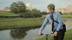 Businessman on folding bicycle with smartphone Stock Footage