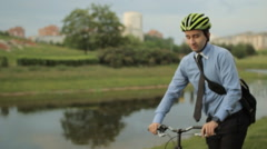Businessman on bicycle with tablet and helmet Stock Footage