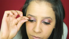 Pretty girl applying fake eye lashes to her eyes in her makeup studio Stock Footage