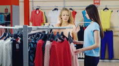Difficult choice right dress. Girls choosing clothes and go out of the frame Stock Footage