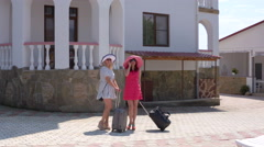 Two women tourists with rolling luggage bags arrived at summer resort hotel Stock Footage