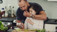 Father teaching his daughter to chop vegetables in kitchen Stock Footage