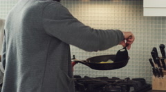 Man preparing a scrambled eggs in kitchen Stock Footage