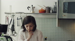 Girl sitting on kitchen worktop and using digital tablet Stock Footage