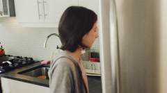 Daughter removing egg carton from fridge in kitchen Stock Footage
