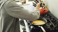 Girl preparing a scrambled egg in kitchen Stock Footage