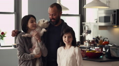 Happy family cuddling with dog in kitchen Stock Footage