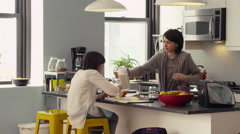 Girl serving breakfast to her sister in kitchen Stock Footage