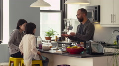 Father and daughters having breakfast in kitchen - stock footage