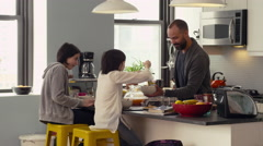 Father and daughters interacting while having breakfast in kitchen - stock footage