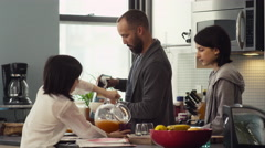 Father serving breakfast to their daughters in kitchen - stock footage