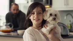 Portrait of happy girl holding a puppy in kitchen Stock Footage