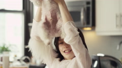 Happy girl playing with puppy in kitchen Stock Footage