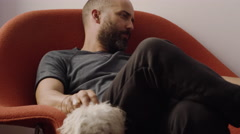 Young man sitting on sofa and petting a puppy at home Stock Footage