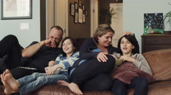Family sitting together on sofa and watching tv in living room - stock footage