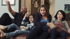 Excited family sitting together on sofa and watching tv in living room Arkistovideo