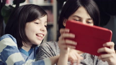 Two girls fighting while using a digital tablet at home Stock Footage