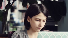 Serious girl using a laptop at home - stock footage