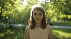Surprisingly beautiful woman in a light blouse on background of summer park - stock footage