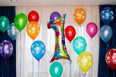 Birthday party, one year balloon sign and many colorful balloons Stock Photos
