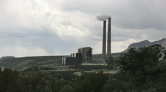 Coal-fired power plant twin smoke stacks emit smoke and steam on cloudy day Stock Footage