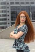 Red-haired woman on the background of office building Stock Photos