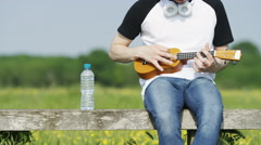 4K Static shot of unseen person playing a ukulele outside in a rural environment Stock Footage