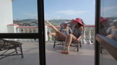 Two women girlfriends having fun together on open terrace at vacation home Stock Footage