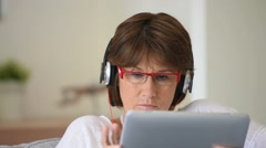 Senior woman listening to music on tablet Stock Footage