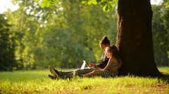 Two girls using tablet in a beautiful park, a warm summer day Stock Footage