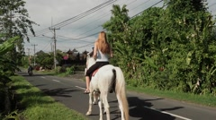 Young woman riding a horse on a street in Bali, Canggu Stock Footage