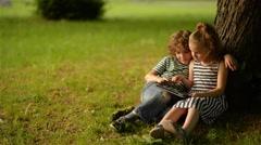 Two cute kids using digital tablet in summer garden Stock Footage