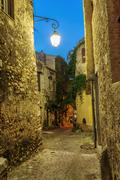 Narrow street in the old town in France at night - stock photo