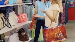 Two friends are choosing to store bags. Pick up the color of their dresses Stock Footage