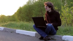 Young Man Uses Laptop Outdoors Stock Footage