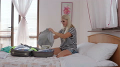 Woman just arrived at hotel room unpacking travel bag on bed Stock Footage