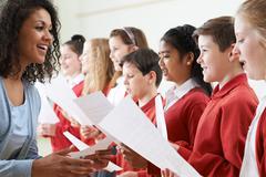 Children In School Choir Being Encouraged By Teacher - stock photo