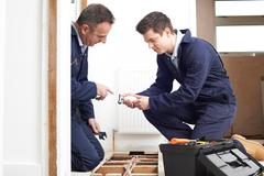 Plumber And Apprentice Fitting Central Heating in House Stock Photos