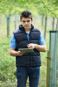Forestry Worker With Digital Tablet Checking Young Trees - stock photo