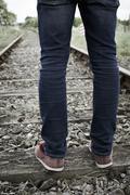 Close-Up Of Man's Feet Standing Between Railway Tracks - stock photo