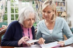 Mature Woman Helping Senior Neighbor With Home Finances Stock Photos