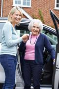 Female Neighbor Giving Senior Woman A Lift In Car - stock photo