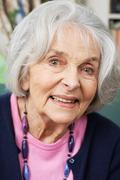 Head And Shoulders Portrait Of Smiling Senior Woman At Home - stock photo